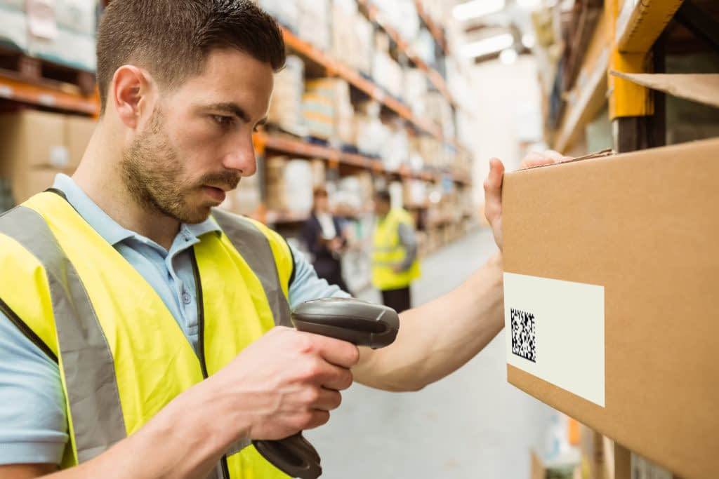 Warehouse worker scans a serialized carton.